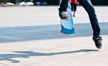 young skater perfoming stunt on his blue board