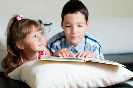 a brother and a sister are lying on a sofa and reading a book Stock Photo - 5576700