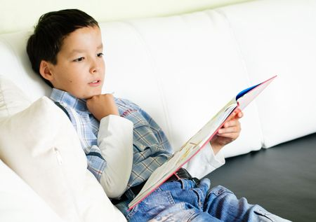 thoughtful little boy sitting on a sofa and reading a book Stock Photo - 5576702