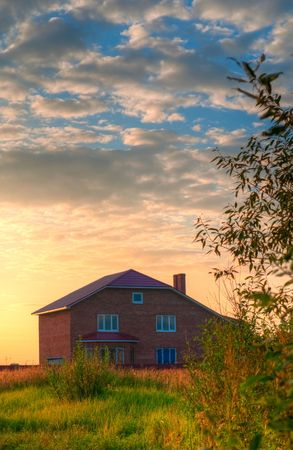 red brick house in the field of yellow flowers with cloudy sky in background Stock Photo - 5576787