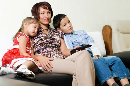 a young mother with two kids, a boy and a girl, is sitting on a sofa and watching a tv Stock Photo - 5738121