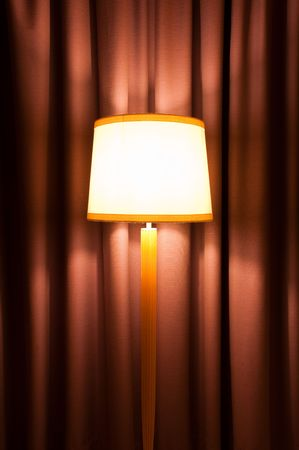 cozy interior with lamp on stand against curtain photo
