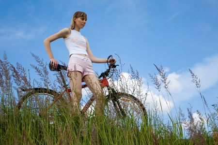 beautiful girl with bicycle standing on the hilltop with blue cloudy sky in background photo