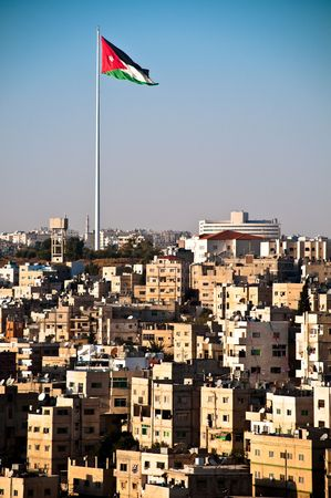 view of city of Amman with giant jordanian flag and blue sky in background photo