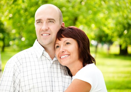 looking away from camera: adult couple of husband and wife in park, both smiling and looking away from camera