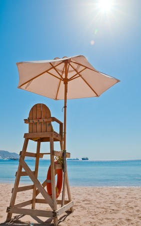 baywatch: beach security chair on the sand near the sea line with bright sun and blue sky in background