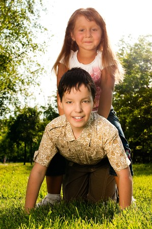 cute little girl sitting on back of her brother, both happy and smiling and looking in camera Stock Photo - 7348281
