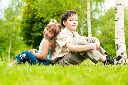 little boy and girl: cute little girl and boy, brother and sister, sitting on green grass back to back, smiling and looking in camera