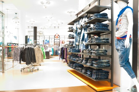 store interior: interior of the modern clothes shop. Image overexposed by intent, all customers blured Stock Photo