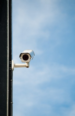 modern security camera on wall of building in street of city with blue sky in background Stock Photo - 7348191