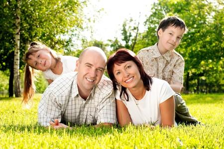 familia feliz de padre y madre y sus hijos: hermano y hermana, sobre césped en el parque. Todos sonriendo y mirando en la cámara  Foto de archivo - 7348277