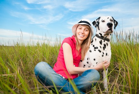 beautiful young woman in hat sitting in grass with her dalmatian dog pet, smiling and looking into the camera