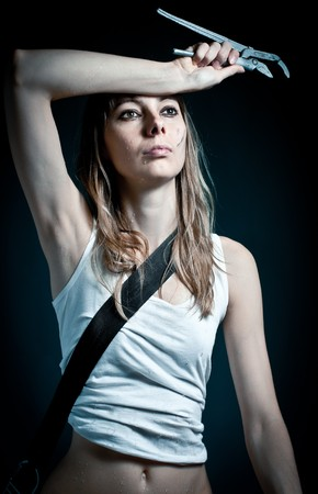young sexy woman  in white undershirt with working tool in hand against dark background photo