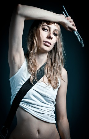 young sexy woman  in white undershirt with working tool in hand looking into the camera. Dark background. photo