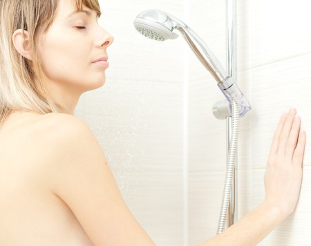 young woman in bathroom  enjoying shower with her eyes closed photo