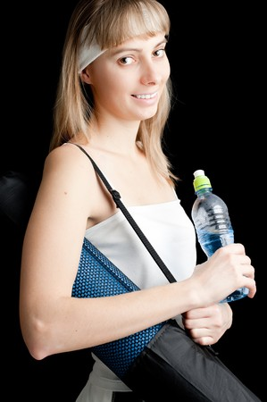 beautiful young woman in sport clothes with bottle of water and with mat for sports photo