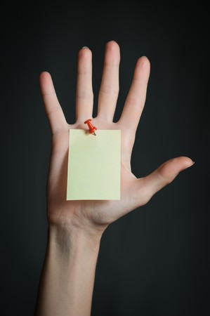 female hand with sticky office note nailed to hand with red pin. Note is blank and yellow. Dark background photo