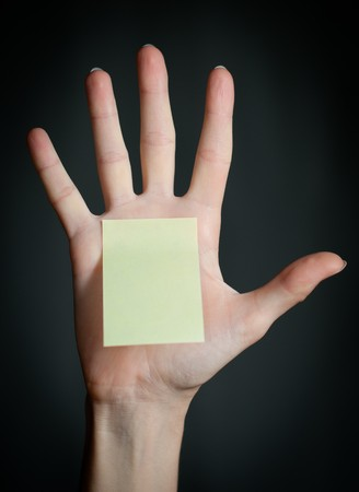 female hand with sticky office note on dark background . Note is blank and yellow photo
