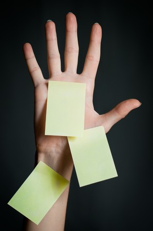 female hand with three office sticky notes on dark background . All notes are blank and yellow photo