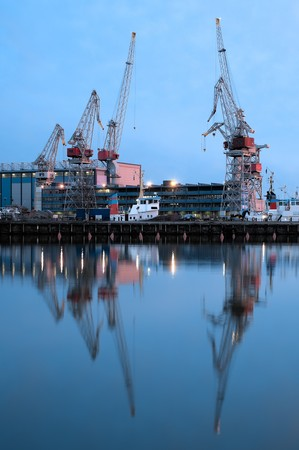sea port cranes with blue night sky in background and water in foreground in Helsinki port, Finland