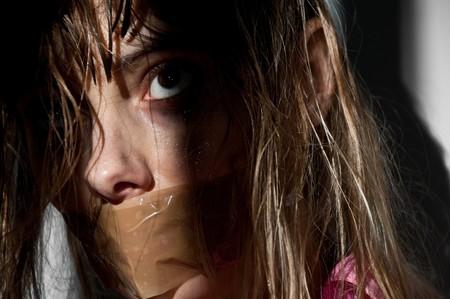 atados: mujer joven tomada rehenes con su boca amordazado