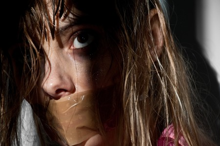 woman prison: young woman taken hostage with her mouth gagged Stock Photo