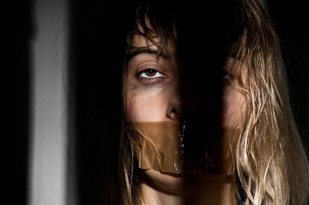 tied woman: young woman taken hostage with her mouth gagged Stock Photo