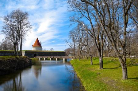 Kuressaare Schloßturm mit blauen Himmel Hintergrund und Wasser mit Reflexionen im Vordergrund (Saarema, Estland)