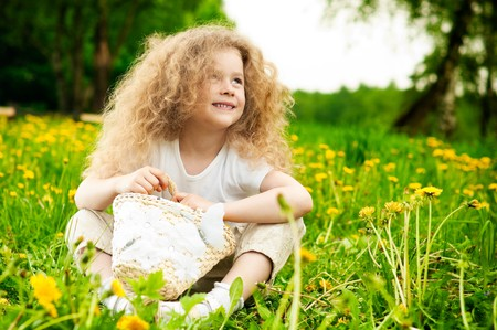 beautiful small girl smiling and sitting on flower field in green grass with basket in hands photo