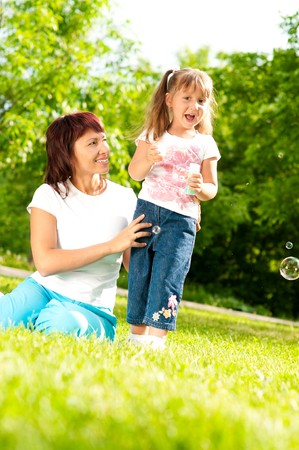 happy young mother sitting in park with her beautiful daughter blowing soap bubbles photo