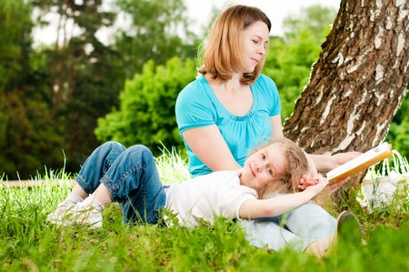 young mother sitting in grass under tree and reading book to her small daughter who is lying on knees of her mother and smiling (focus on child)