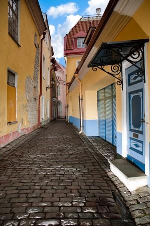 tallin: narrow cosy street in center of old european town. Blue cloudy sky in background. Tallin, Estonia, Europe.