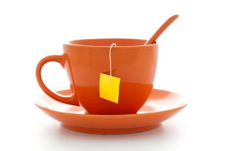 naranja taza de té con platillo y bolsa de té dentro con etiqueta amarilla vacía  Foto de archivo