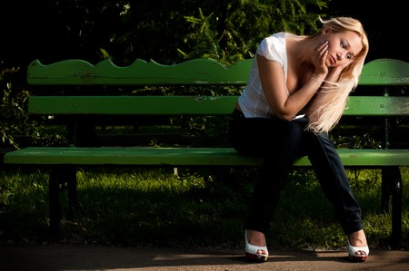 beautiful sad young woman sitting on the green bench in the park photo