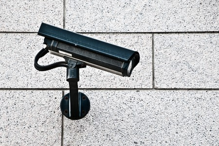 modern security camera on wall of building in street of city photo