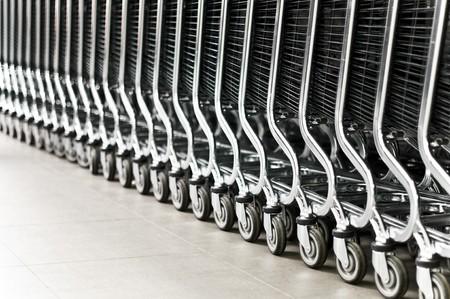 carro supermercado: fila de vac�os carritos de compras en el supermercado grande (extremadamente profundidad de campo, centrarse en la cuarta rueda de derecha)