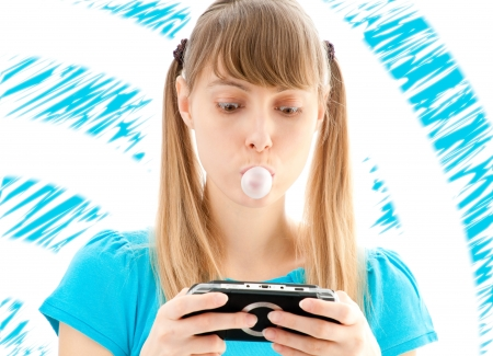 young girl with colored background making bubble of chewing gum and playing video game photo