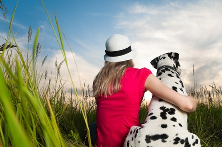 beautiful young woman in hat sitting in grass with her dalmatian dog pet with their backs to camera. Sunset cloudy sky in background and green grass in foreground. Stock Photo