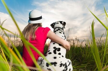 dalmatier: mooie jonge vrouw in de hoed op gras met haar Dalmatische honden huis dier met de rug naar de camera. Zons ondergang bewolkte hemel achtergrond en groen gras in de voorgrond.  Stockfoto