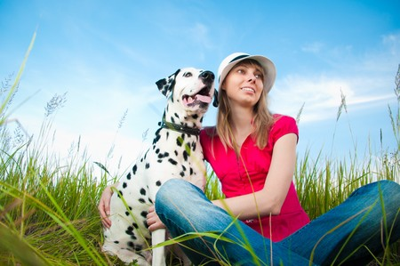 beautiful young woman in hat sitting in grass with her dalmatian dog pet and smiling. Blue sky in background and green grass in foreground. Stock Photo