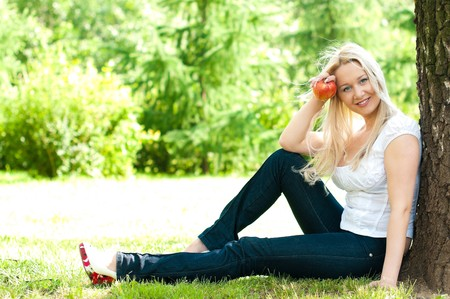 young beautiful woman sitting under the tree in the park and eating apple photo