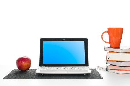 office work desk with laptop computer, pile of books, cup of coffee and apple Stock Photo - 7289809