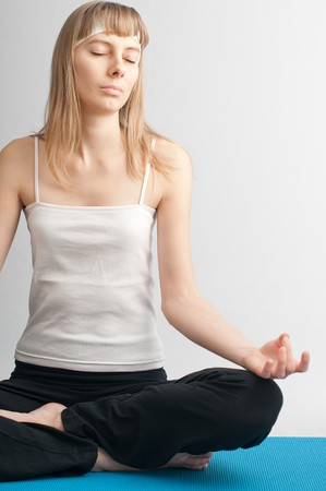 Fit young woman doing yoga exercise sitting in lotus pose Stock Photo - 7294775