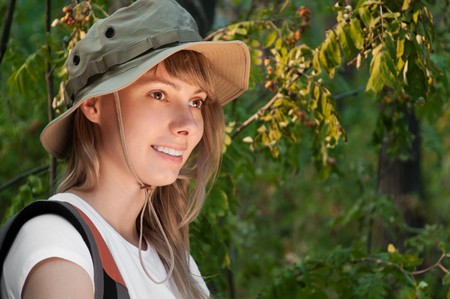 looking away from camera: beautiful young woman standing  in forest with backpack, smiling and looking away from camera
