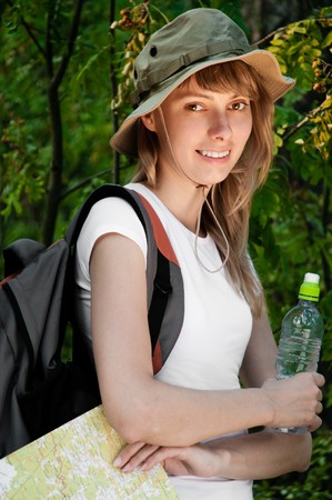 beautiful young woman standing in forest with backpack, map and bottle of water, smiling and looking in camera Stock Photo - 8094726