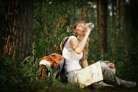 beautiful young woman sitting under tree in forest with backpack and map, drinking water with her eyes closed Stock Photo