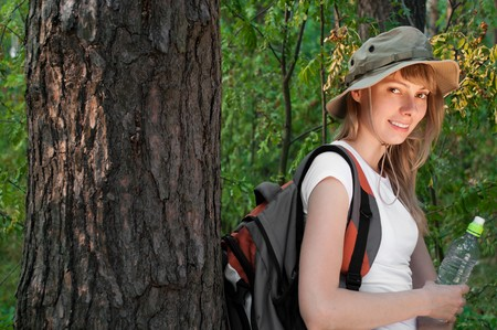 beautiful young woman standing near the tree in forest with backpack and bottle of water, smiling and looking in camera Stock Photo - 8094728
