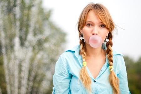 beautiful young student girl blowing bubble from chewing gum and looking into the camera photo