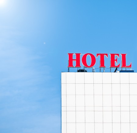 red hotel sign on roof of building, blue sky in background, lots of copy space