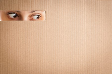 peep: surprised woman eyes looking through the hole in cardboard
